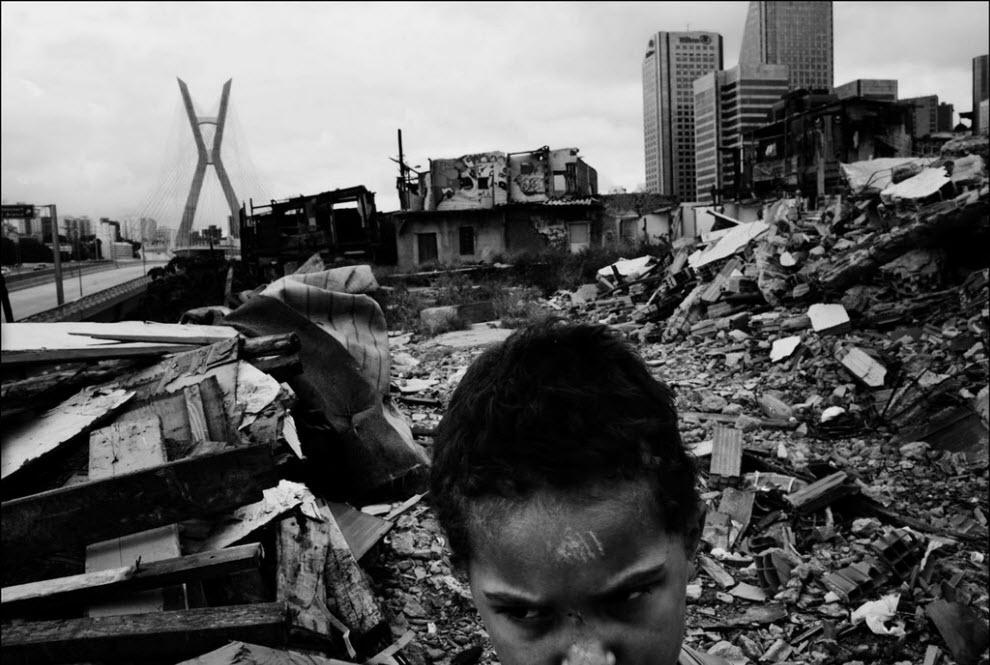23) Измаель дош Сантош играет с булыжником, оставшимся после разрушения домов.