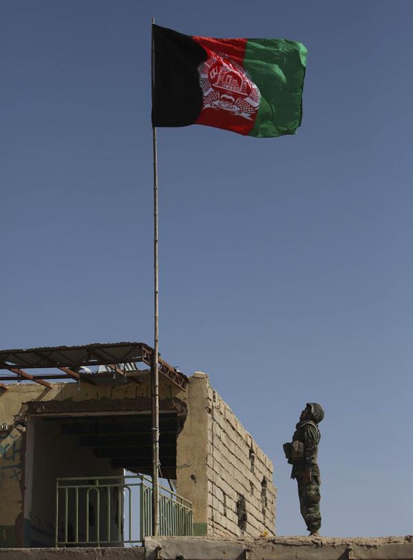 24. Солдат афганской армии отдает честь национальному флагу, поднятому на здании на рынке в Маржахе. (AP Photo/Altaf Qadri)