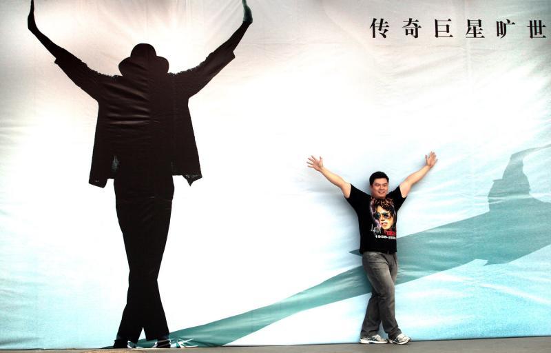 24. Китайский киноман позирует рядом с плакатом Майкла Джексона в преддверии его фильма в Пекине. (UPI Photo/Stephen Shaver)