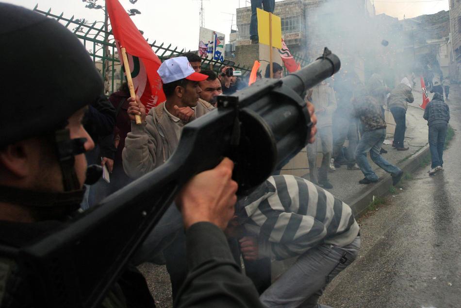 24) Израильский солдат выстреливает гранаты со слезоточивым газом в толпу протестующей палестинской молодежи, 25 февраля, 2010. Беспорядки в Хевроне продолжаются с четверга, именно тогда Израиль объявил, что несколько святынь, расположенных на территории Палестины, будут включены в список национального наследия еврейского народа. Немногим ранее президент Палестины Махмуд Аббас предупреждал, что за таким решением может последовать «религиозная война». (AP Photo/Nasser Shiyoukhi)