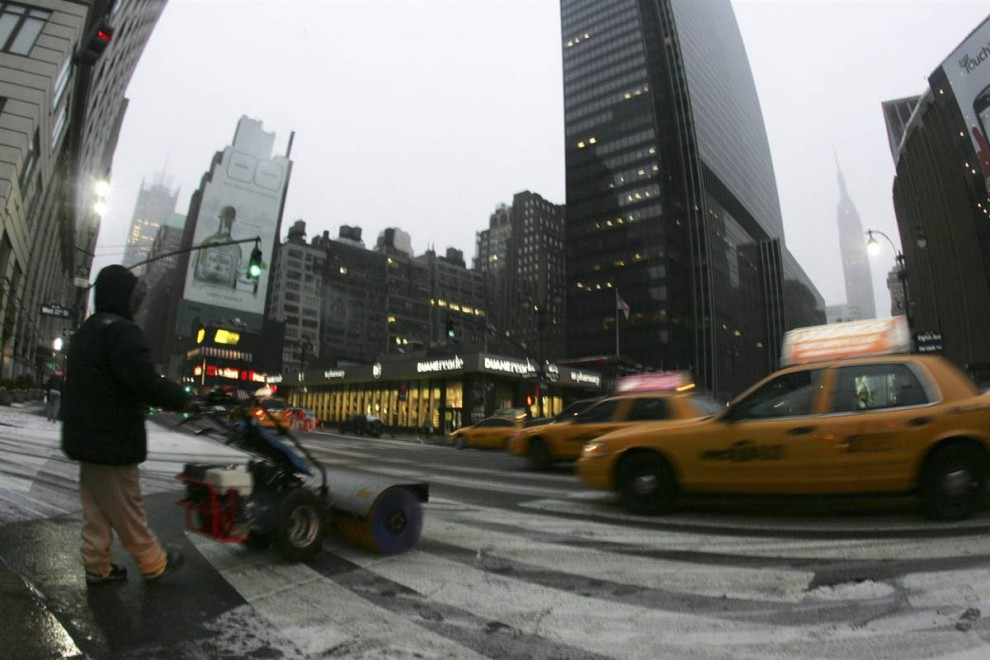 24. Томас Малдомадо (слева) толкает перед собой снегоочиститель недалеко от Эмпайр-Стейт-Билдинг 6 февраля в Нью-Йорке. (Caleb Jones / AP)