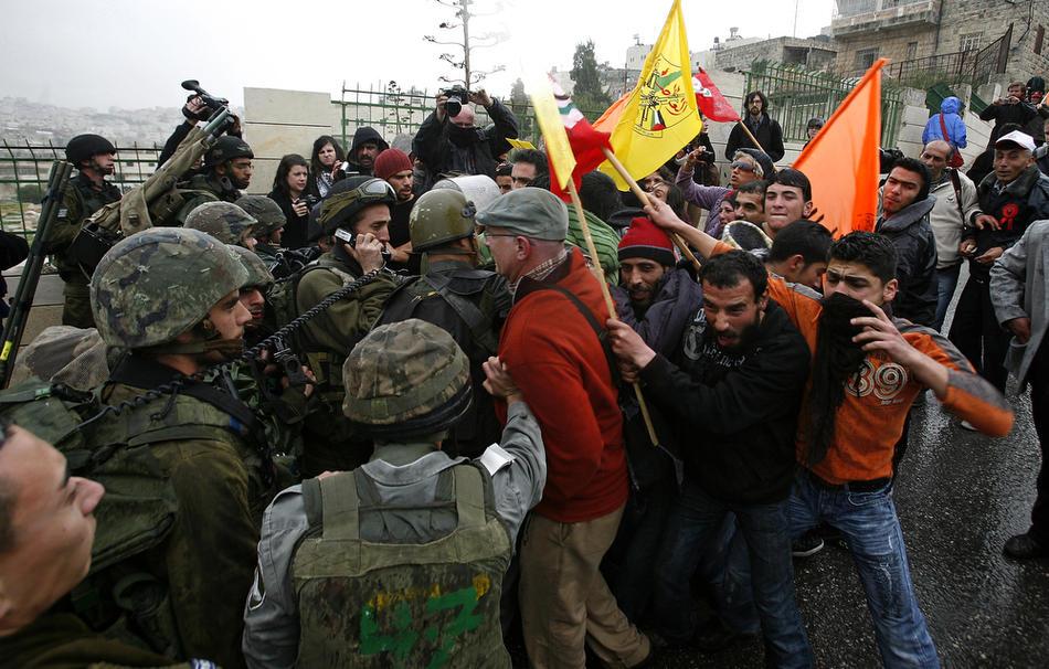 25) Израильские солдаты пытаются разогнать толпу протестующих палестинцев и иностранных активистов, собравшихся около Пещеры Праотцев у Мечети Аль-Ибрахими, Хеврон, 25 февраля, 2010. Около 100 палестинских демонстрантов несколько дней учиняли беспорядки в Хевроне. Это произошло после того, как президент Израиля Беньямин Нетаньяху объявил о намерениях включить Пещеру Праотцев и Гробницу праматери Рахели, расположенные на территории Палестины, включить в список национального наследия еврейского народа и произвести их реставрацию. (AFP PHOTO/HAZEM BADER)