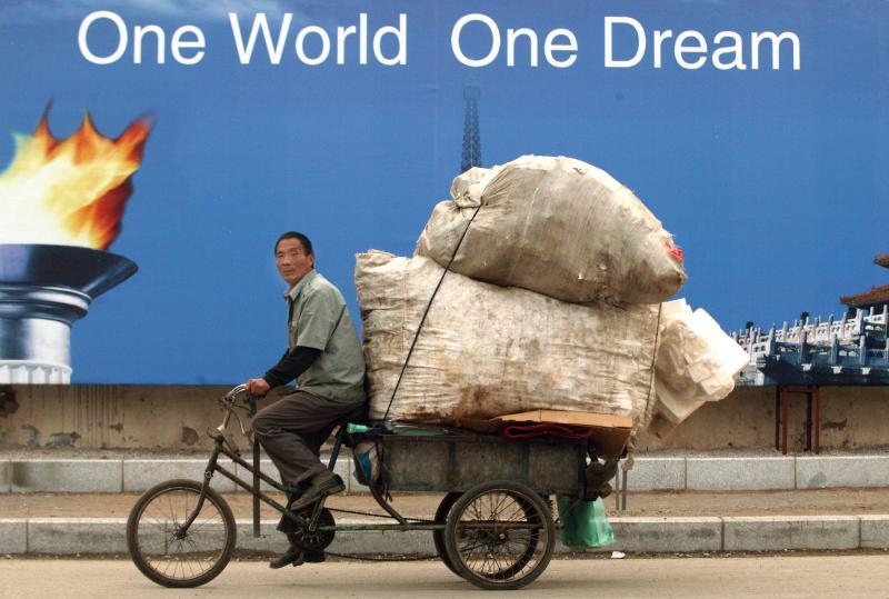 25. Мигрант везет мусор мимо рекламного щита в Пекине. (UPI Photo/Stephen Shaver)