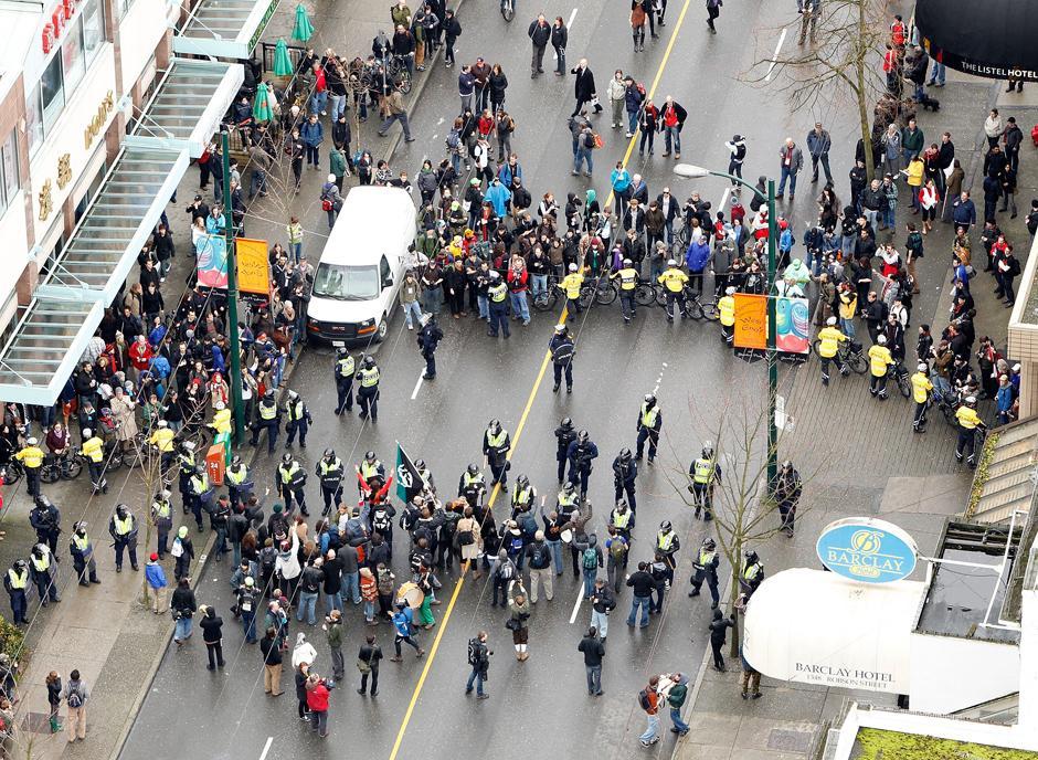 14) Полицейский кордон разделил улицу. В ходе столкновений с полицией было ранено несколько сотрудников правопорядка и арестованы десятки демонстрантов.