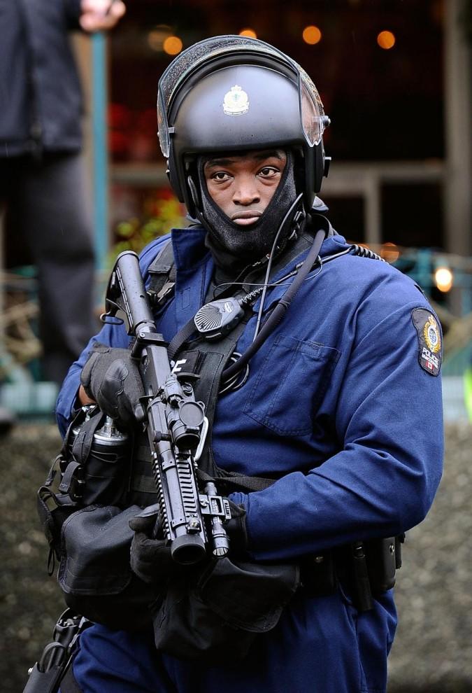 12) Полицейский в полной экипировке для борьбы с уличными беспорядками наблюдает за протестующими.