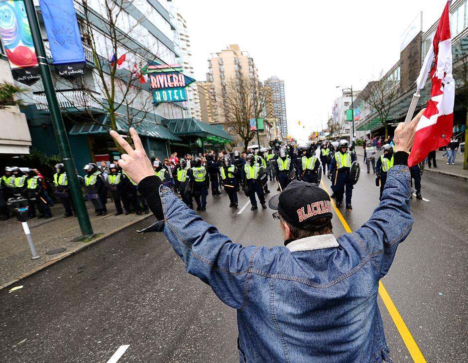 10) Один из демонстрантов держит частично сожженый флаг Канады. В протестах приняли участие радикально настроенные молодежь, взрослые и старики.