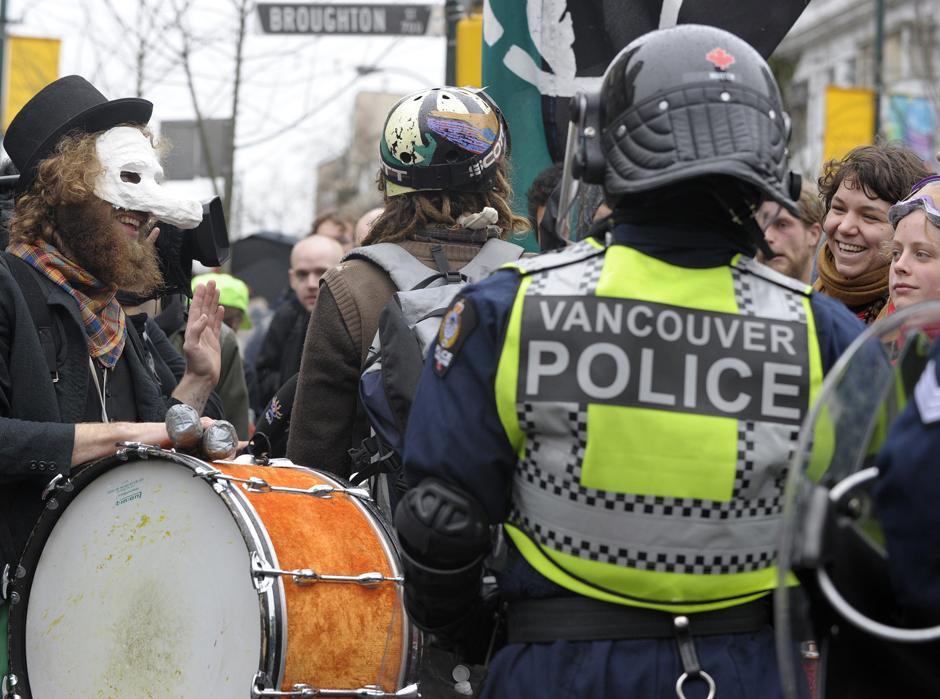8) Полицейский на фоне демонстрантов во время акции протеста в центре Ванкувера.