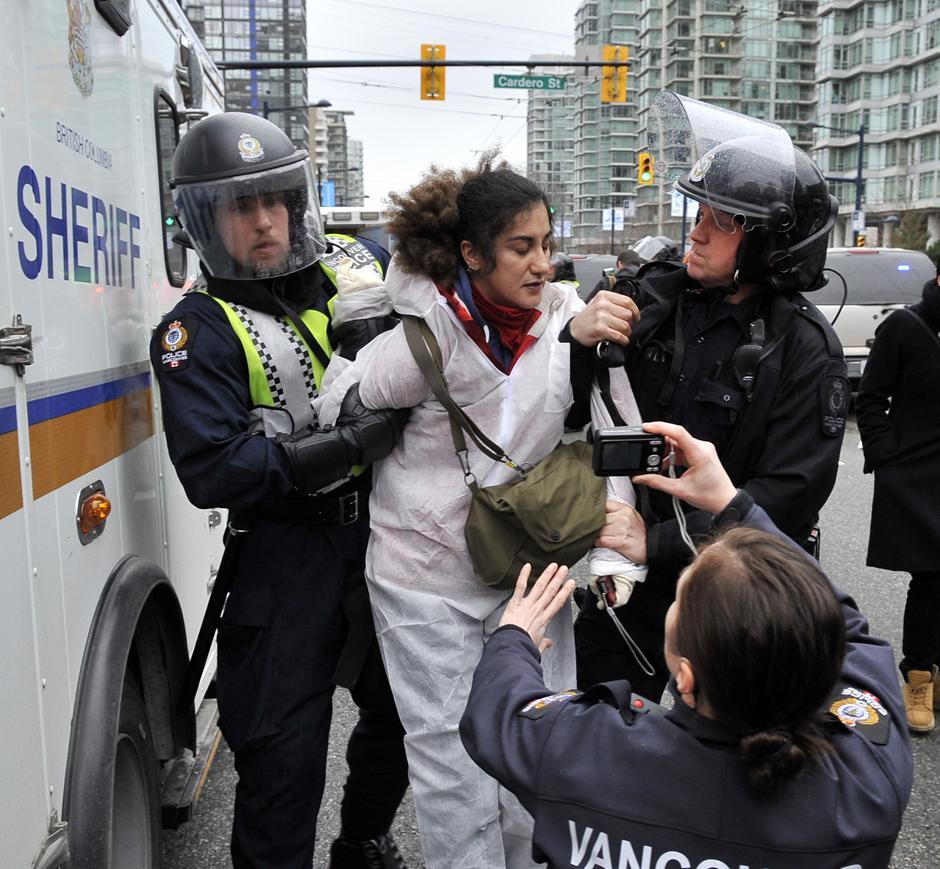7) Женщина-офицер полиции Ванкувера фотографирует задержанную.