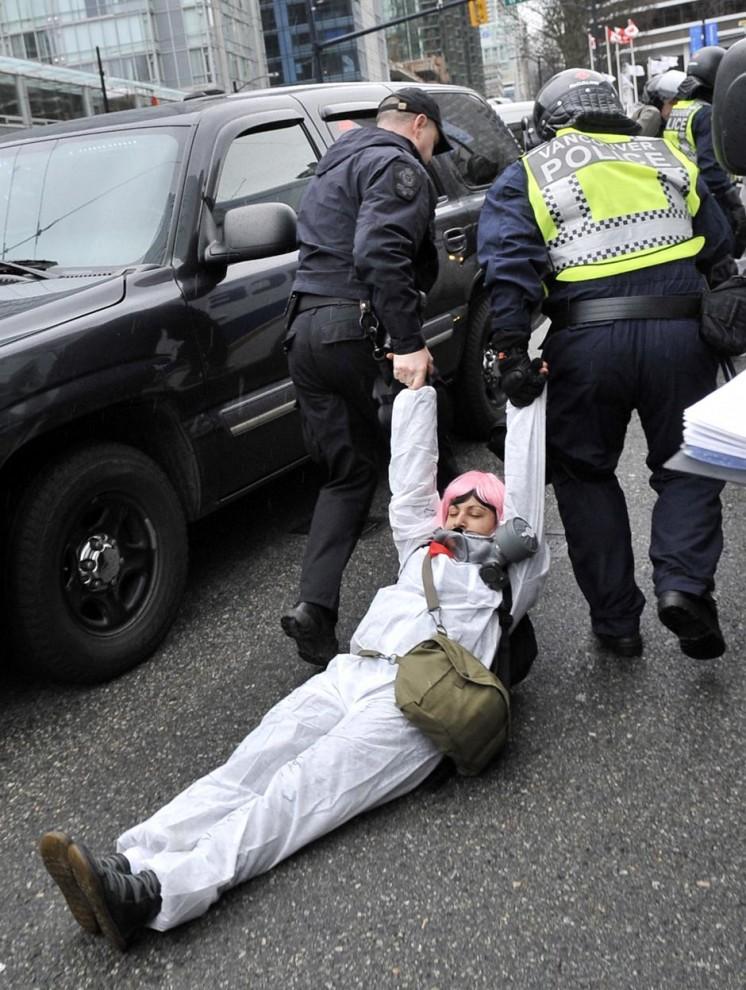 6) Полицейские волокут девушку с противогазом во время демонстраций в центре Ванкувера.