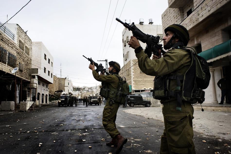 26) Израильские солдаты занимают позиции во время столкновений с палестинскими демонстрантами в Хевроне, 25 февраля, 2010. Около 100 палестинских демонстрантов несколько дней учиняли беспорядки в Хевроне. Это произошло после того, как президент Израиля Беньямин Нетаньяху объявил о намерениях включить Пещеру Праотцев и Гробницу праматери Рахели, расположенные на территории Палестины, включить в список национального наследия еврейского народа и произвести их реставрацию. (AFP PHOTO/ALESSIO ROMENZI)