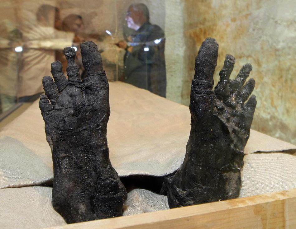 27. Ноги фараона Тутанхамона в специальном стеклянном ящике с климат-контролем. Настоящее лицо знаменитого египетского фараона было представлено публике впервые с момента его странной кончины более 3000 лет назад. Мумию фараона переместили из саркофага в гробнице, где его находка в 1922 году стала настоящей сенсацией. (CRIS BOURONCLE/AFP/Getty Images)