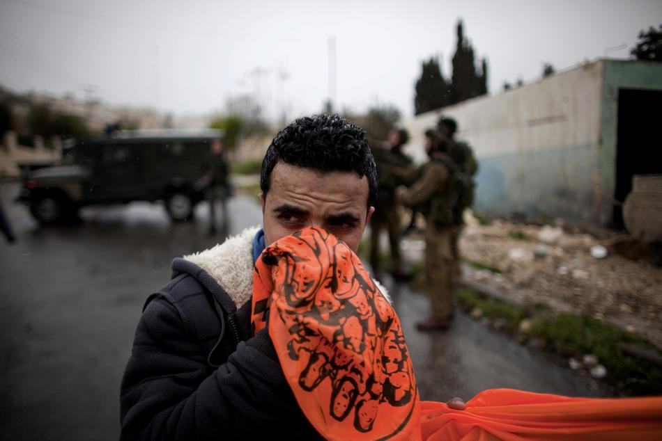 27) Один из палестинских участников акции протеста закрывает лицо, пытаясь тем самым защититься от слезоточивого газа, выпущенного во время столкновений в Хевроне, 25 февраля, 2010. Около 100 палестинских демонстрантов несколько дней учиняли беспорядки в Хевроне. Это произошло после того, как президент Израиля Беньямин Нетаньяху объявил о намерениях включить Пещеру Праотцев и Гробницу праматери Рахели, расположенные на территории Палестины, включить в список национального наследия еврейского народа и произвести их реставрацию. (AFP PHOTO/MARCO LONGARI)