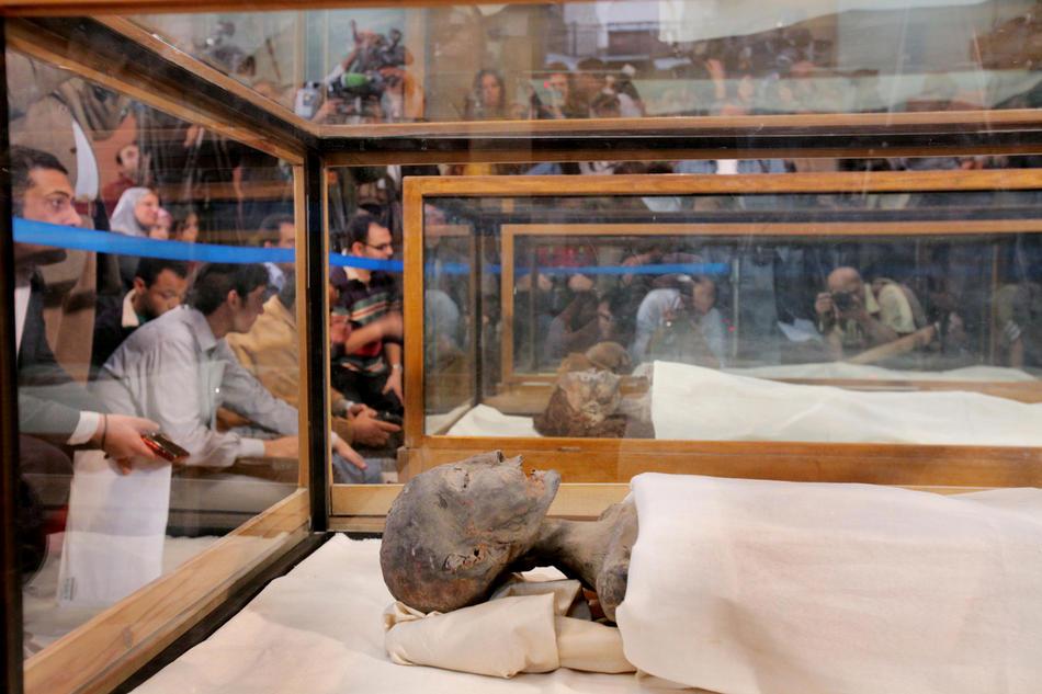 28. На этом снимке канала «Discovery» можно увидеть мумии (начиная с ближней) матери Тутанхамона, бабушки Тутанхамона и отца Тутанхамона, представленные репортерам на пресс-конференции археологом Захи Хавассом в музее Каира 17 февраля 2010 года. Два года анализов ДНК и томографий мумии Тутанхамона и 15 других фараонов помогло установить генеалогическое древо королевской семьи, доказав, что отцом Тутанхамона был фараон Эхнатон, и матерью – его родная сестра. (AP Photo/Discovery Channel, Shawn Baldwin)
