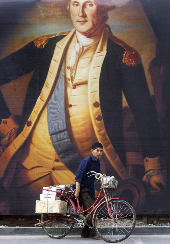 28. Китайский курьер несет свой велосипед перед огромным плакатом президента США Джорджа Вашингтона в центре Пекина. Многие китайские компании – от агентств недвижимости до инвестиционных фирм – используют для рекламы известные политические фигуры или звезд спорта. (UPI Photo/Stephen Shaver)