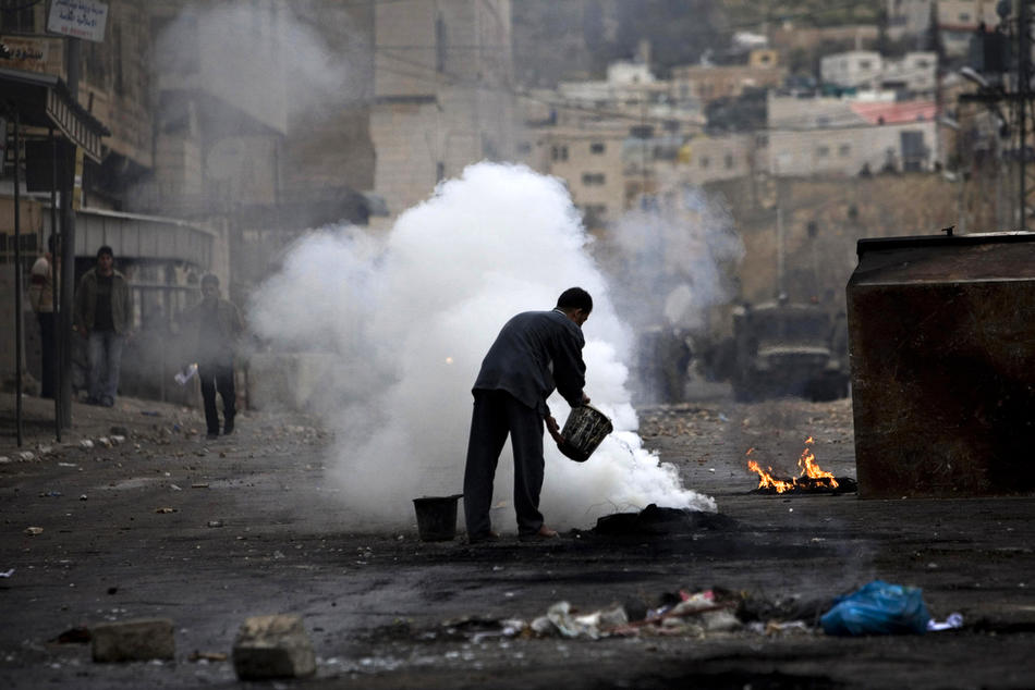 29) Палестинский мирный житель пытается потушить горящие покрышки, оставленные после столкновений в Хевроне между израильскими солдатами и палестинскими демонстрантами. Беспорядки в Хевроне продолжаются с четверга, именно тогда Израиль объявил, что несколько святынь, расположенных на территории Палестины, будут включены в список национального наследия еврейского народа. Немногим ранее президент Палестины Махмуд Аббас предупреждал, что за таким решением может последовать «религиозная война». (AP Photo/Bernat Armangue)