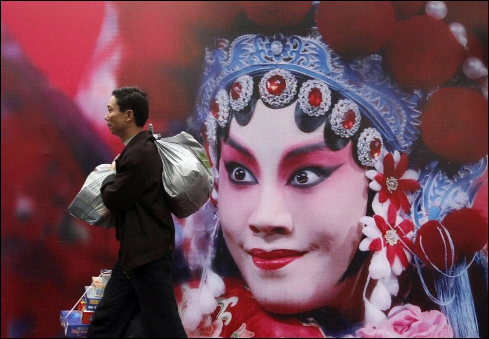 28) Пассажир идет мимо постера-афиши Китайского оперного театра. (Reuters/Joe Tan)