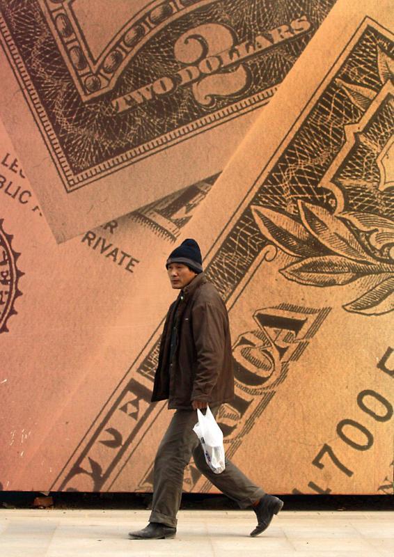29. Китаец проходит мимо большого рекламного плаката с американскими долларами в центре Пекина. (UPI Photo/Stephen Shaver)