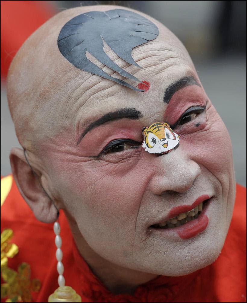 32) Актер с наклейкой тигра танцует в время первого дня празднования китайского нового года. (Reuters/Andy Wong)
