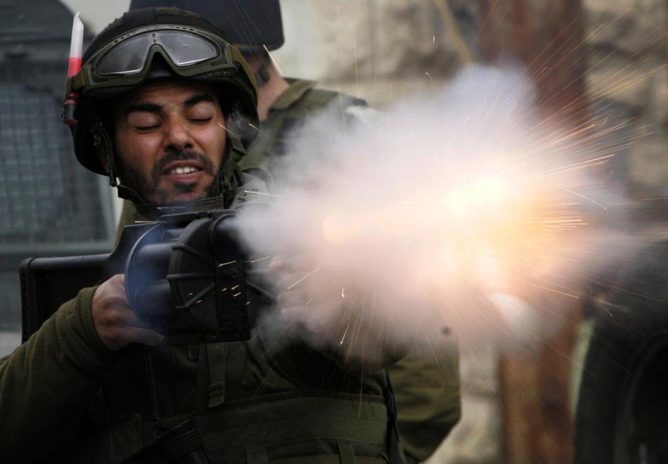 03) Израильские солдаты выпускают слезоточивый газ с целью пресечь нападения палестинской молодежи, забрасывающей солдат камнями, во время столкновений в Хевроне, 25 февраля, 2010. Беспорядки в Хевроне продолжаются с четверга, именно тогда Израиль объявил, что несколько святынь, расположенных на территории Палестины, будут включены в список национального наследия еврейского народа. Немногим ранее президент Палестины Махмуд Аббас предупреждал, что за таким решением может последовать «религиозная война». (AP Photo/Nasser Shiyoukhi)