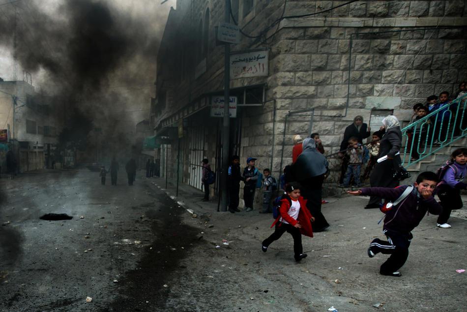 04) Палестинские дети покидают школу, так как беспорядки приближаются, и запах жженой резины и слезоточивого газа становится невыносимым, 25 февраля, 2010. Палестинцы проводят акции протеста в Хевроне с тех пор, как 21 февраля 2010 года было объявлено, что Пещера Праотцев и Гробница праматери Рахели, расположенные на территории Палестины, будут включены в список национального наследия еврейского народа. Палестинцы возмущены действиями Израиля. ООН, США и некоторые европейские страны пытаются уладить конфликт. (Rina Castelnuovo/The New York Times)
