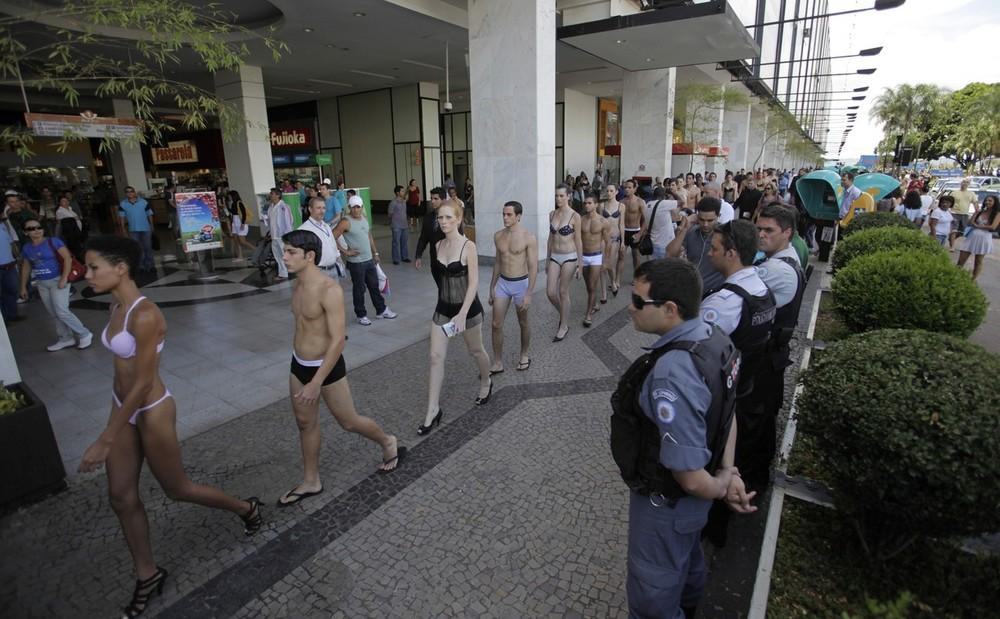 3) Модели под пристальным наблюдением полиции проходят мимо торгового центра в Бразилиа. (REUTERS/Ricardo Moraes)