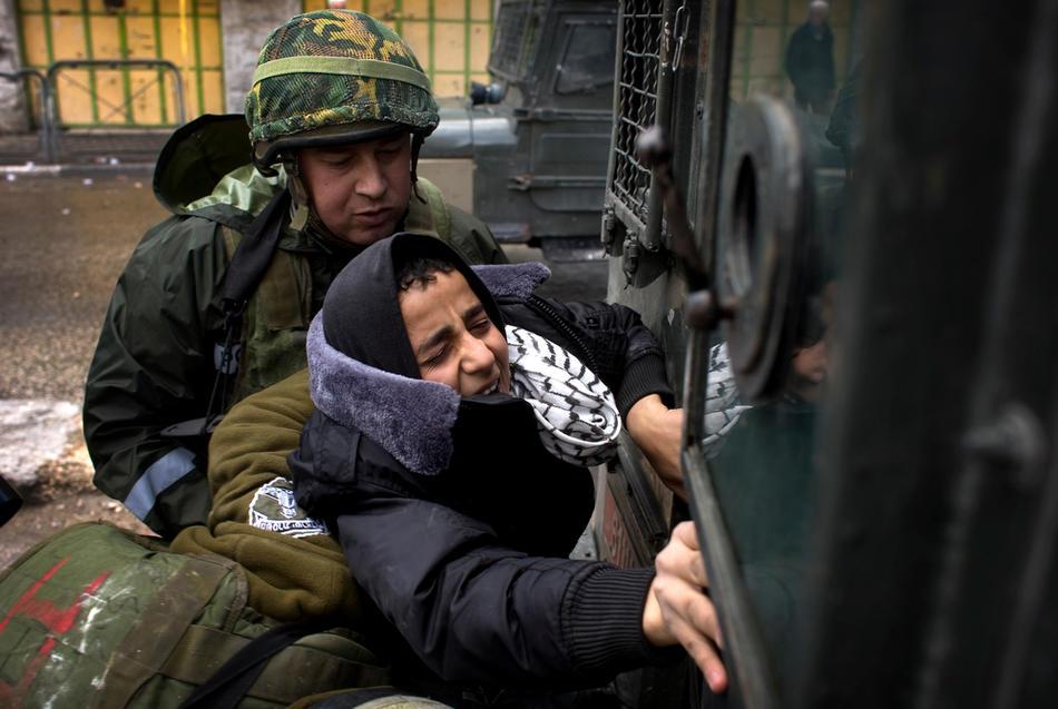 05) Израильские солдаты производят аресты участников акций протеста в Хевроне, 26 февраля, 2010. Премьер Палестины Салам Файяд молился в Пещере Праотцев, когда шел пятый день столкновений, несмотря на то, что Израиль собирается объявить эту и еще несколько святынь национальным наследием еврейского народа. (AFP PHOTO/DAVID FURST)