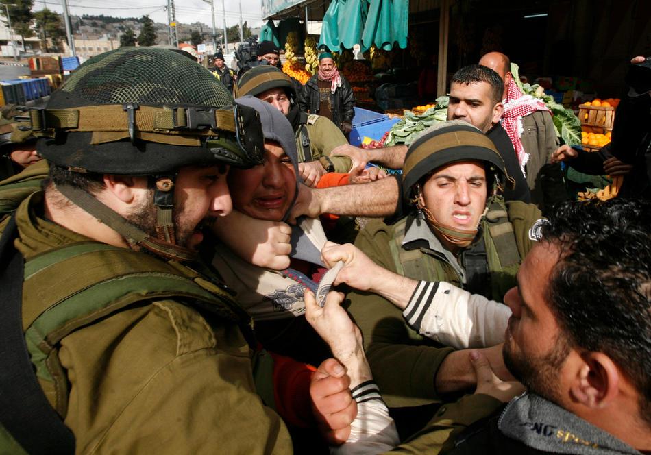 06) Израильские солдаты производят аресты участников акций протеста в Хевроне, 26 февраля, 2010. В Хевроне пять дней шли акции протеста против решения Израиля объявить Пещеру Праотцев своим национальным наследием. Пещера находится на территории Мечети Аль-Ибрахими. (AFP PHOTO / HAZEM BADER)
