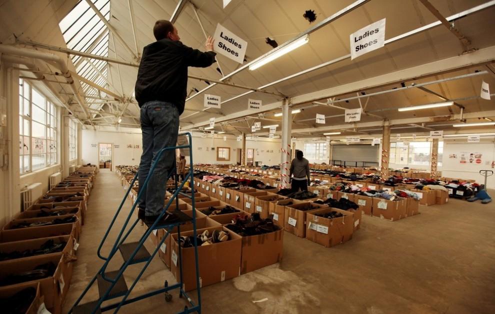 6. Работник склада развешивает таблички перед распродажей, которая состоится в субботу, 6 февраля 2010. (Photo by Oli Scarff/Getty Images)