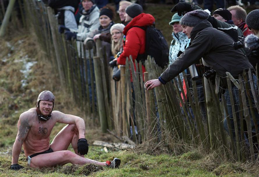 1. Зритель предлагает участнику соревнования «Tough Guy» («Крутой парень») попить. Снимок сделан в Саут Пертон Фарм в Волверхэмптоне, Англия. (AP Photo/Simon Dawson)