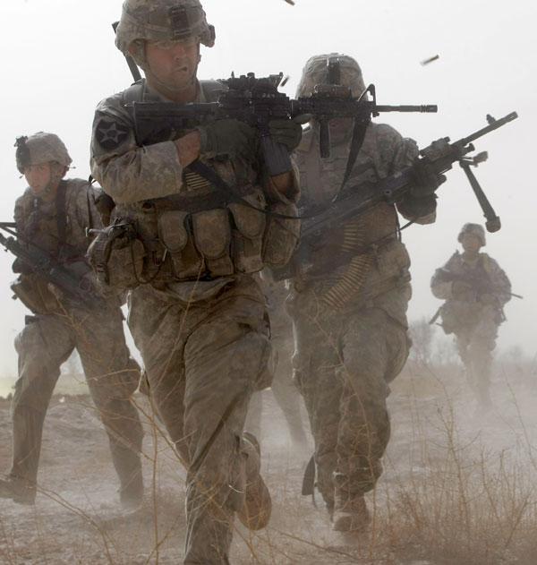 1. Солдат отстреливается, пока другие бегут в укрытие во время перестрелки с боевиками в районе Бадула Калп, на западе Лашкар Гах в провинции Гильменд. Этот район находится рядом с Маржахом, где ВМФ США проводит операцию против организации «Талибан». (AP Photo/Pier Paolo Cito)