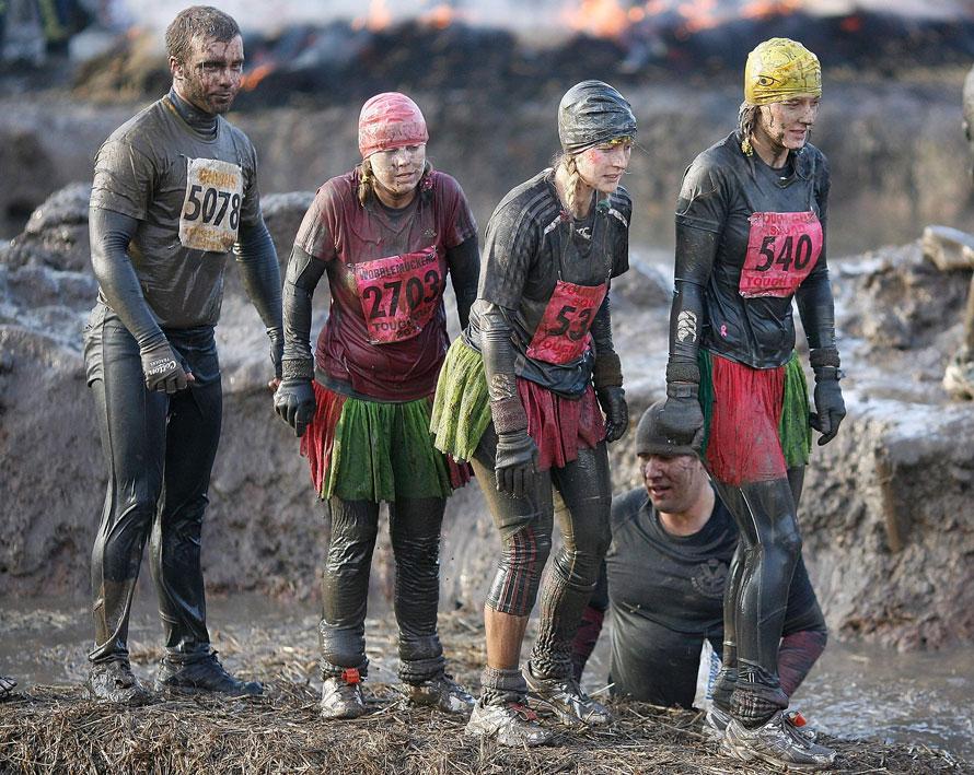 4. Уставшие участники соревнования «Tough Guy» преодолевают препятствие в Саут Пертон Фарм в Стаффордшире, Англия. (AP Photo/Simon Dawson)
