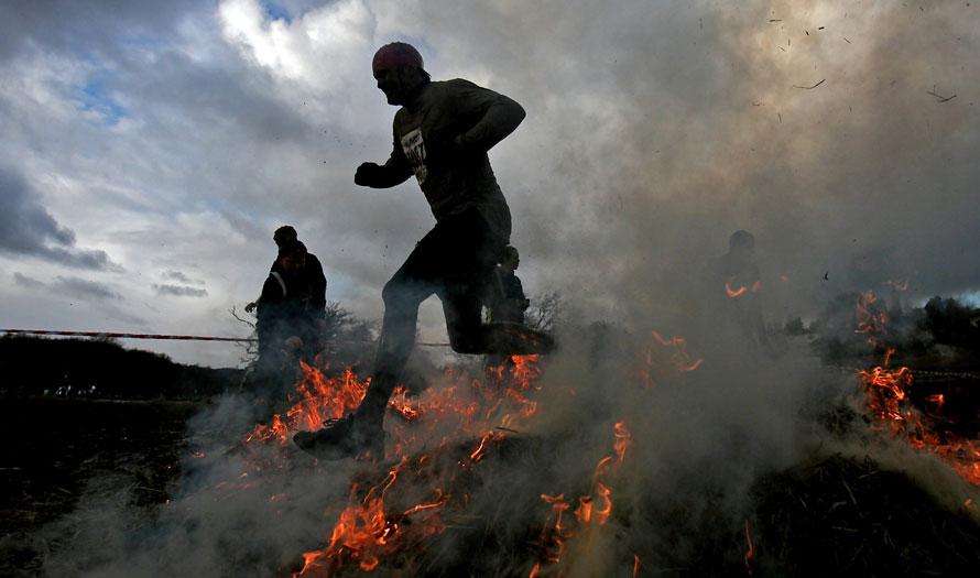 5. Участник соревнования «Tough Guy» бежит через огонь в Саут Пертон Фарм, Волверхэмптон, Англия. (AP Photo/Simon Dawson)