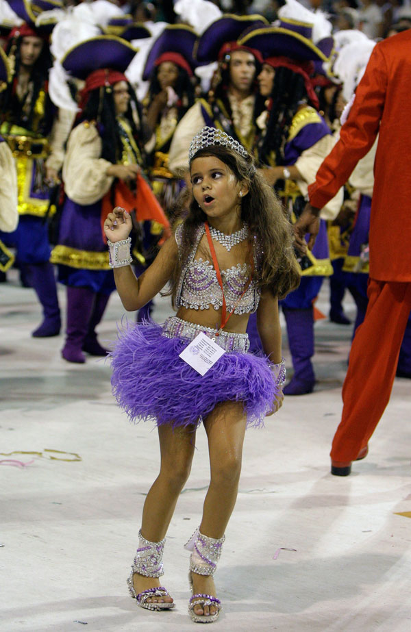 1) 7-летняя Джулия Лира из школы самбы Вирадуро танцует на карнавале в Самбадроме в Рио-де-Жанейро. Суд постановил, что 7-летняя девочка имеет право танцевать самбу перед тысячами зрителей, что обычно делают более взрослые и раскрепощенные модели. (AP Photo/Martin Mejia)
