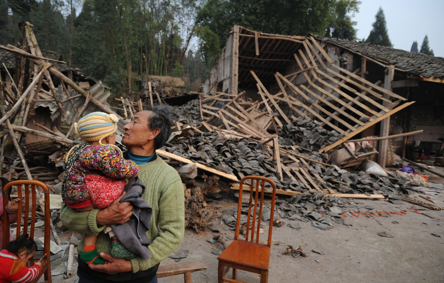 7. Мужчина с внуком на руках стоит перед своим домом, разрушенным в результате землетрясения в 5.2 балла в Суининге, провинция Сычуань, Китай. (AP Photo/Xinhua, Jiang Hongjing)