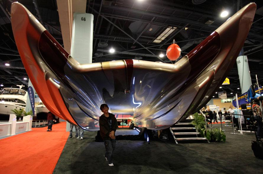8. Мальчик проходит под 15-метровым катером под названием «50-ая страсть», сделанным компанией «Statement Marine», на Международной выставке лодок в Майями Бич, Флорида. В катере есть кабина на воздушной подушке, вертолетные газотурбинные двигатели. Катер разгоняется до скорости 289 км в час и стоит 1,5 миллиона долларов. (AP Photo/Lynne Sladky)