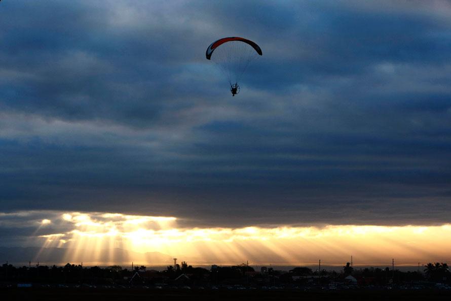 11. Парашютист парит над полем на рассвете в качестве «бонуса» в последний день четырехдневного фестиваля воздушных шаров в городе Ангелес, провинция Пампанга, Манила. (AP Photo/Bullit Marquez)