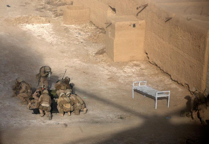 20) На этом фото, сделанном через стекло военно-медицинского вертолета, морпехи и солдаты прикрывают раненых от пыли, поднятой в воздух приземляющимся вертолетом в Маржахе, провинция Гильменд. (AP Photo/Brennan Linsley)