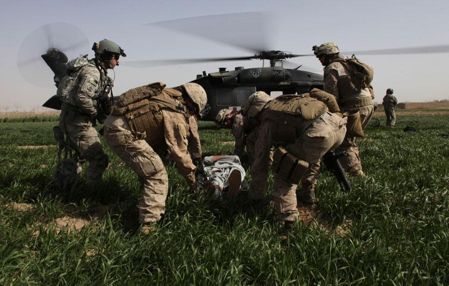 19) Афганца с огнестрельным ранением несут в вертолет оперативной группы «Пегас» в Маржахе, провинция Гильменд. Слева штабной сержант и медик Роберт Б. Каудрей. Аэромедицинская группа «Пегаса» была несколько раз обстреляна из гранатометов и автоматов во время операции по поддержанию американских и афганских войск в борьбе против боевиков «Талибана». (AP Photo/Brennan Linsley)