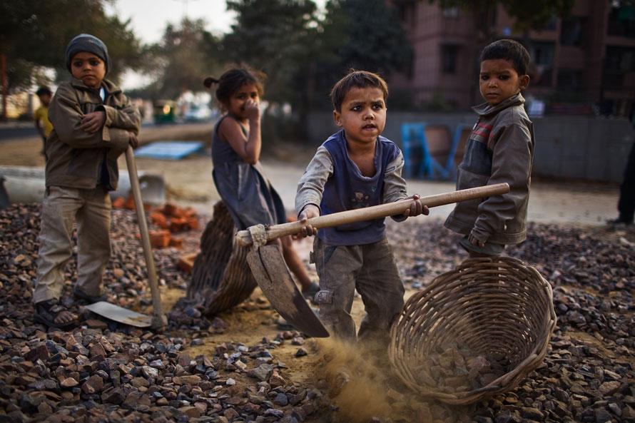12. Индийские дети работают вместе со своими родителями на стройплощадке перед стадионом «Джавахарлал Нехру» в Нью-Дели. (Photo by Daniel Berehulak/Getty Images)