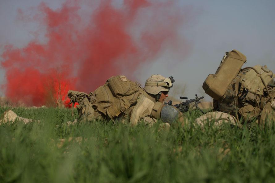 18) Морпех из третьего батальона 6-го полка укрывается в маковом поле во время перестрелки с талибами в городе Маржах. (AP Photo/David Guttenfelder)