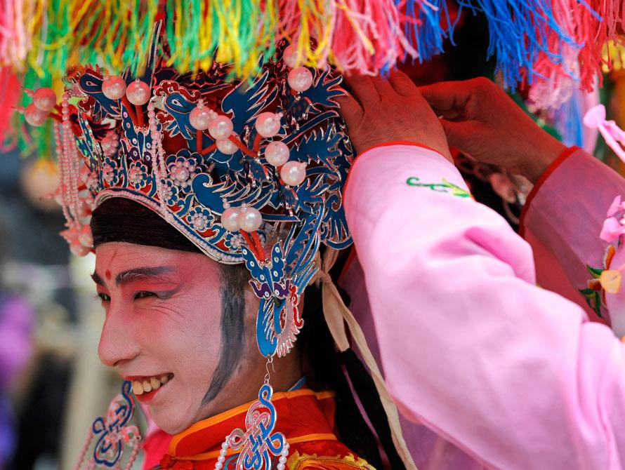 14. Артист готовится к первому дню празднования лунного Нового года в районе Пекина Цяньмэнь. Миллионы китайцев начали празднование Нового года тигра в воскресенье. (AP Photo/Andy Wong)