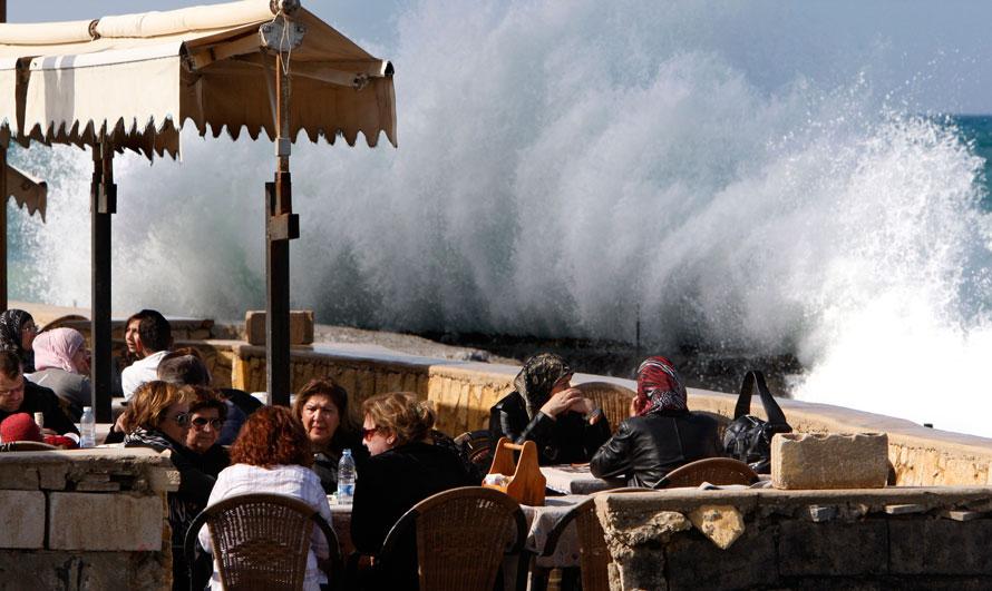15. Ливанцы сидят в пляжном кафе в Бейруте на фоне разбивающихся о пирс волн. (AP Photo/Hussein Malla)