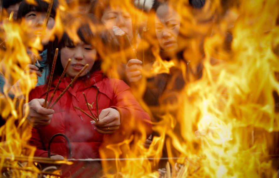 16. Верующие зажигают ладан в храме Лама в первый день китайского нового года в Пекине. (AP Photo/Vincent Thian)