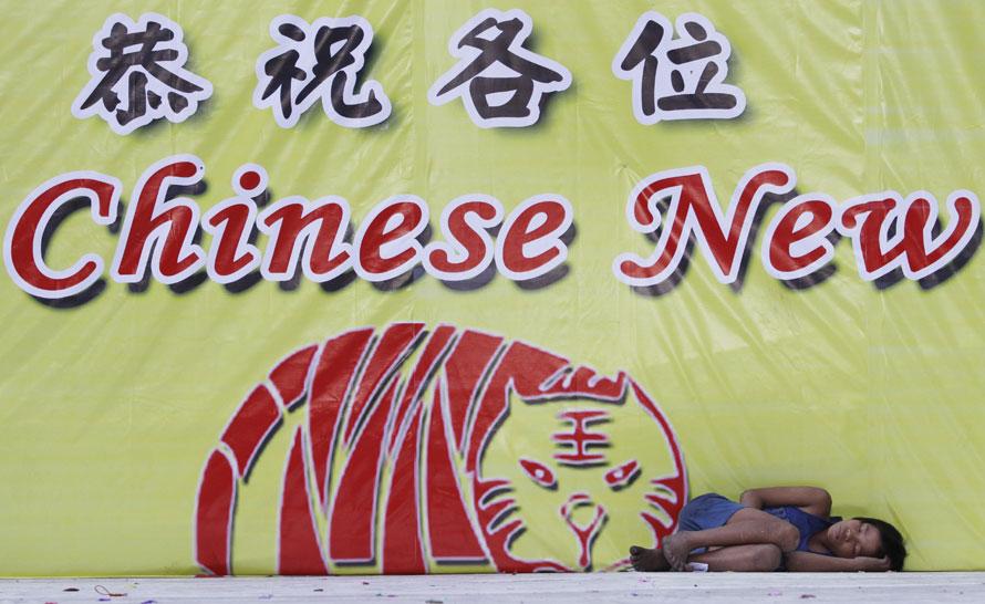 17. Филиппинец спит перед огромным плакатом с надписью «Счастливого китайского нового года» в районе чайнатауна в Маниле. Многие туристы специально приехали сюда, чтобы отпраздновать китайский лунный новый год тигра. (AP Photo/Aaron Favila)
