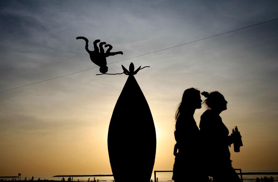 18. Две женщины с прохладительными напитками проходят мимо статуи на пляже, где люди наслаждаются приятным вечером у Средиземного моря, в Тель-Авиве. В прибрежных районах температура достигла 31 градуса по Цельсию. (AP Photo/Ariel Schalit)