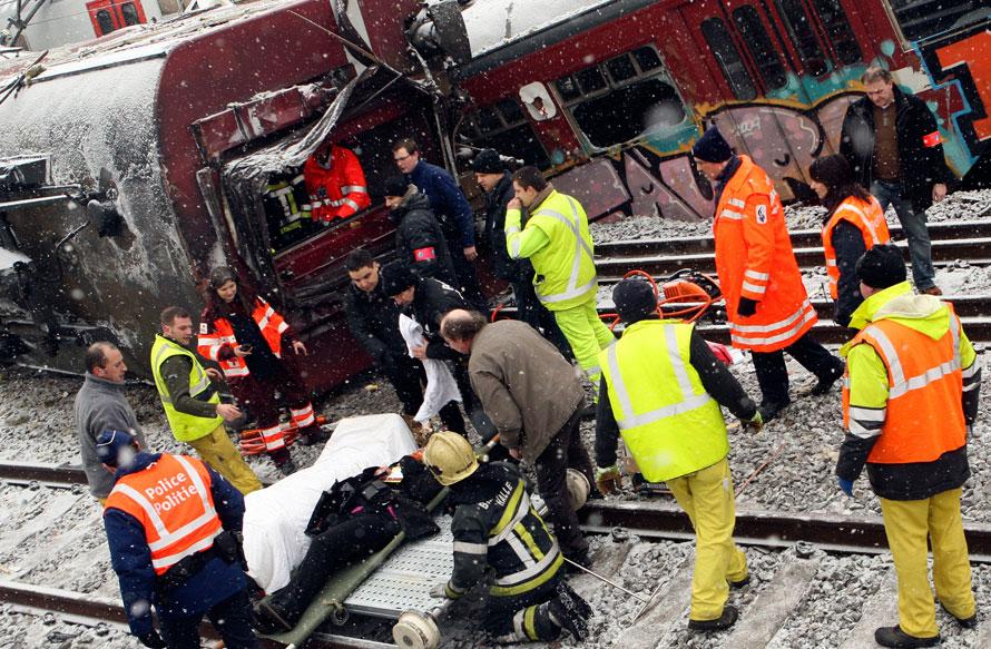 9) Спасатели помогают раненой пассажирке поезда в Буйзингене, Бельгия. Два поезда столкнулись лоб в лоб в пригороде Брюсселя, в результате чего погибло 20 человек. (AP Photo/Yves Logghe)