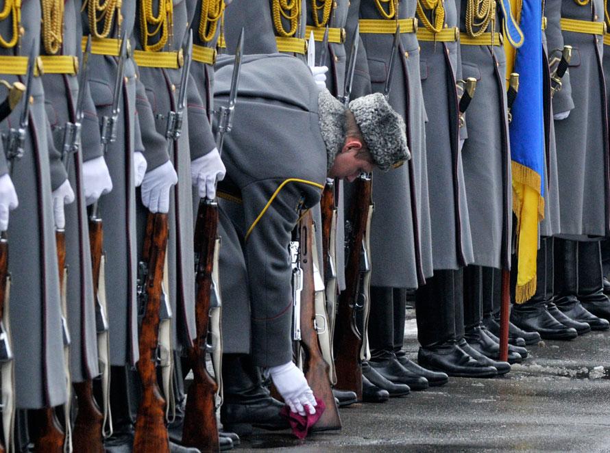 7) Член украинского почетного караула вытирает сапог во время поминальной церемонии о погибших в войне в Афганистане (1979-1989) в Киеве. (AP Photo/Sergei Chuzavkov)