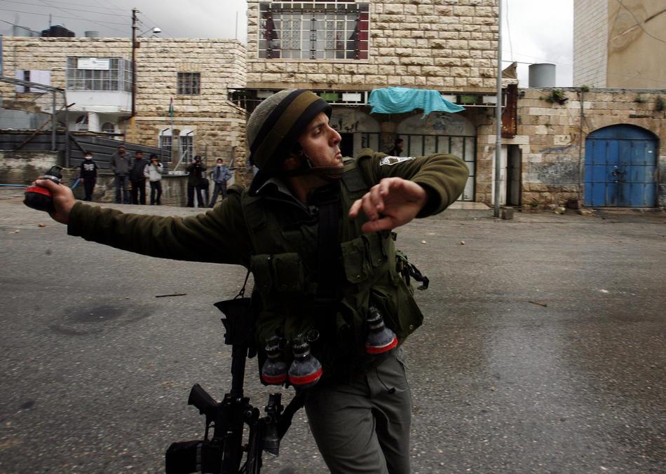 08) Израильский солдат бросает гранату со слезоточивым газом в палестинцев во время столкновений в Хевроне, 26 февраля, 2010. Акции протеста шли пять дней после решения Израиля объявить Пещеру Праотцев своим национальным наследием. Пещера находится на территории Мечети Аль-Ибрахими. (AFP PHOTO / HAZEM BADER)