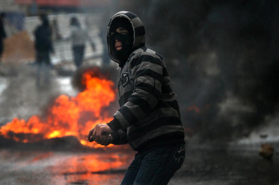 09) Палестинцы забрасывают камнями израильских солдат в Хевроне, 26 февраля, 2010. Премьер Палестины Салам Файяд посетил могилу Абрахама, которая считается священной как у мусульман, так и у евреев. После молитвы премьер заявил репортерам, что он осуждает действия Израиля. Палестинцы устраивали яростные беспорядки в Хевроне после того, как было объявлено, что Пещера Праотцев и Гробница праматери Рахели, расположенные на территории Палестины, будут включены в список национального наследия еврейского народа. (AP Photo/Tara Todras-Whitehill)