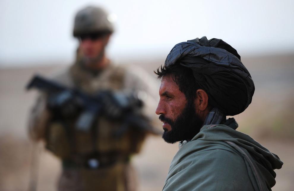 3. Афганский крестьянин стоит на фоне морпеха из первого батальона шестого полка подразделения «Чарли», который патрулирует территорию рядом с лагерем «Huskers» на окраине Маржаха 26 февраля. (CHRISTOPHE SIMON/AFP/Getty Images)